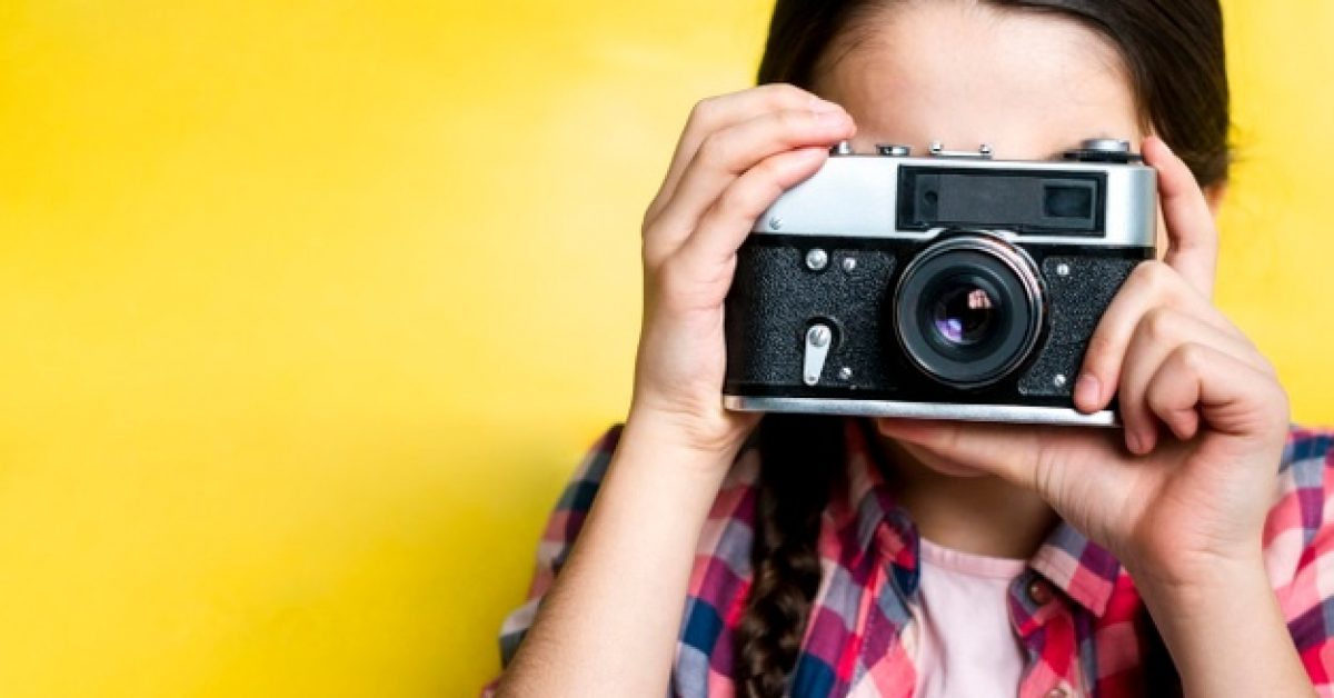 young-girl-taking-picture-with-retro-camera_23-2148456327